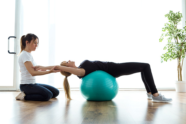 Physiotherapist helps female patient stretch on a medicine ball