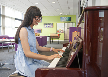 A student plays piano in the common room at Bellerbys Brighton