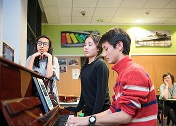 Students at Bellerbys College play the piano as part of an enrichment activity