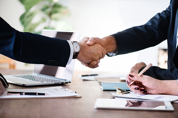 Two business people shake hands in a meeting
