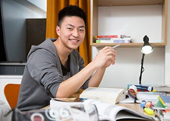 smiling student in accommodation at desk